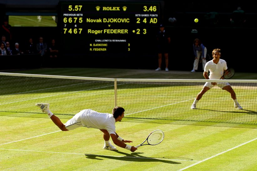LONDON, ENGLAND - JULY 06: Novak Djokovic of Serbia dives to make a return as Roger Federer of Switzerland stands at the net during the Gentlemen's Singles Final match on day thirteen of the Wimbledon Lawn Tennis Championships at the All England Lawn Tennis and Croquet Club on July 6, 2014 in London, England. (Photo by Al Bello/Getty Images)